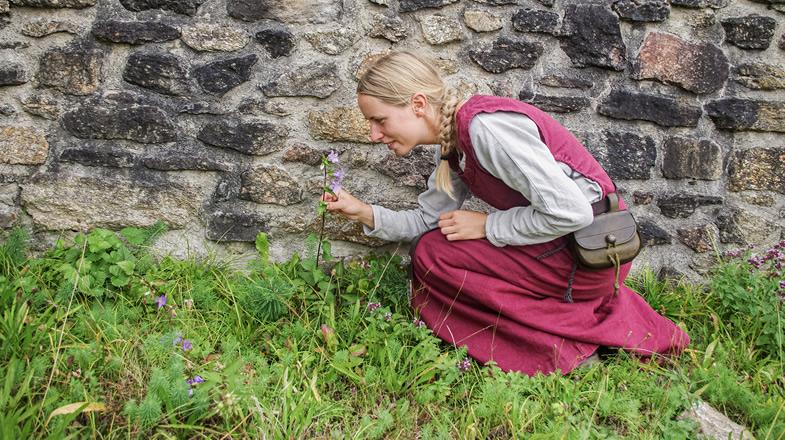 Anna beim Bestaunen einer Blume