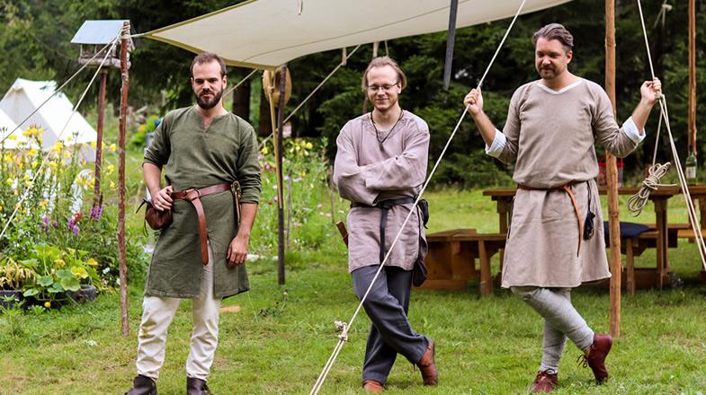 Andreas, Benjamin und Florian verfolgen ein Spiel auf der Wiese
